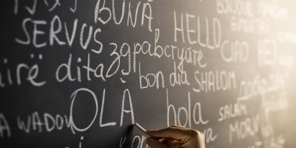 Hello in many languages written with chalk on blackboard