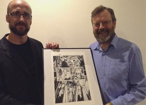 Kieron presents Stephen with an original art page from the book THREE