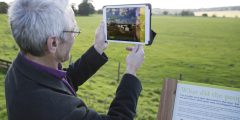 A man looks at an iPad showing a roman town overlaying existing fields