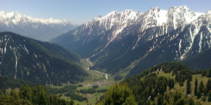 View_of_Aru_Village_enclosed_by_snow_clad_mountains_from_top_of_Birzamal