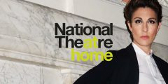 A woman standing next to the words 'National Theatre At Home'