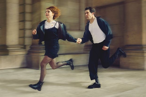 A young woman and man run down a street holding hands