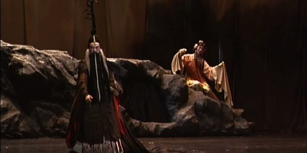 A man dressed as a Chinese sorcerer stands on a stage, while someone else watches.