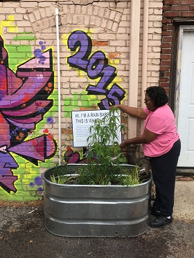A photograph of a resident working on the rain barrel project