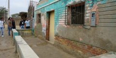 A photograph of a home owner showing the flood depth level in front of his house, Piura, Peru.