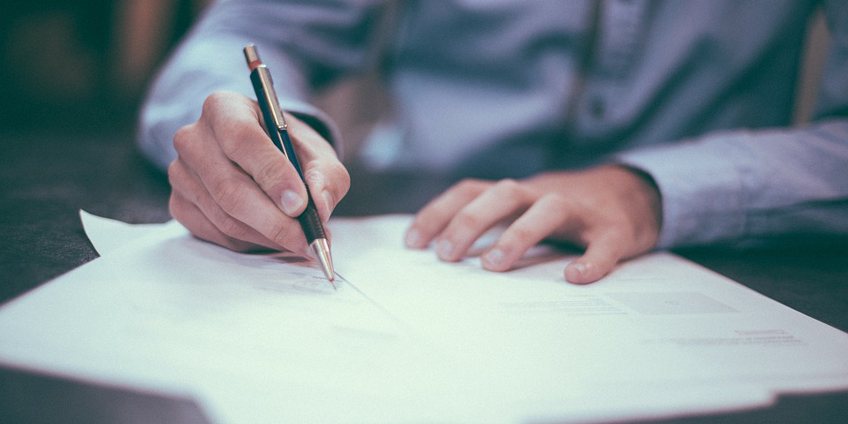 A man dressed smartly writing out his CV with a pen and paper