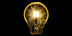 luminating yellow light bulb lit up in a dark room