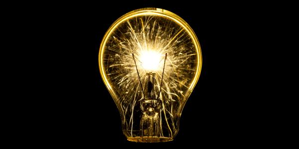 luminating yellow light bulb lit up in a dark room