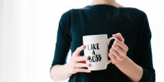 "A woman holding a mug which quotes on it ""like a boss"" to symbolise entrepreneurship"