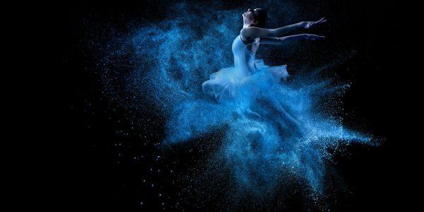 Ballet dancer colour image contrast. Vibrant neon blue colour contrast of ballet clothing onto a black background