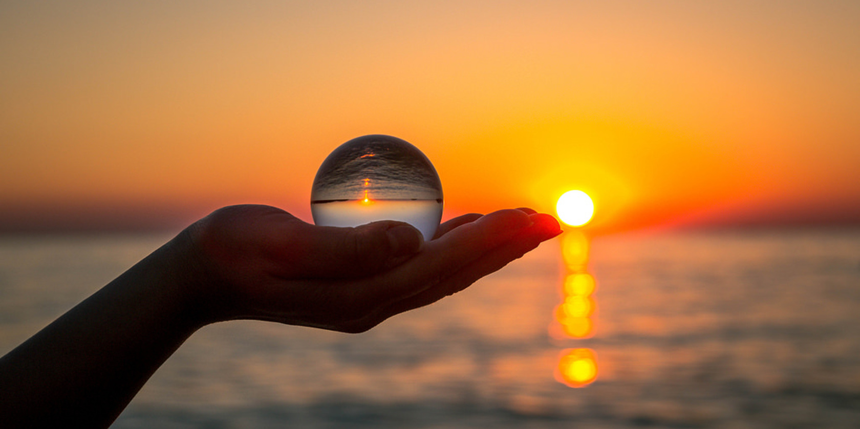 someone holding a glass ball in the the sunset