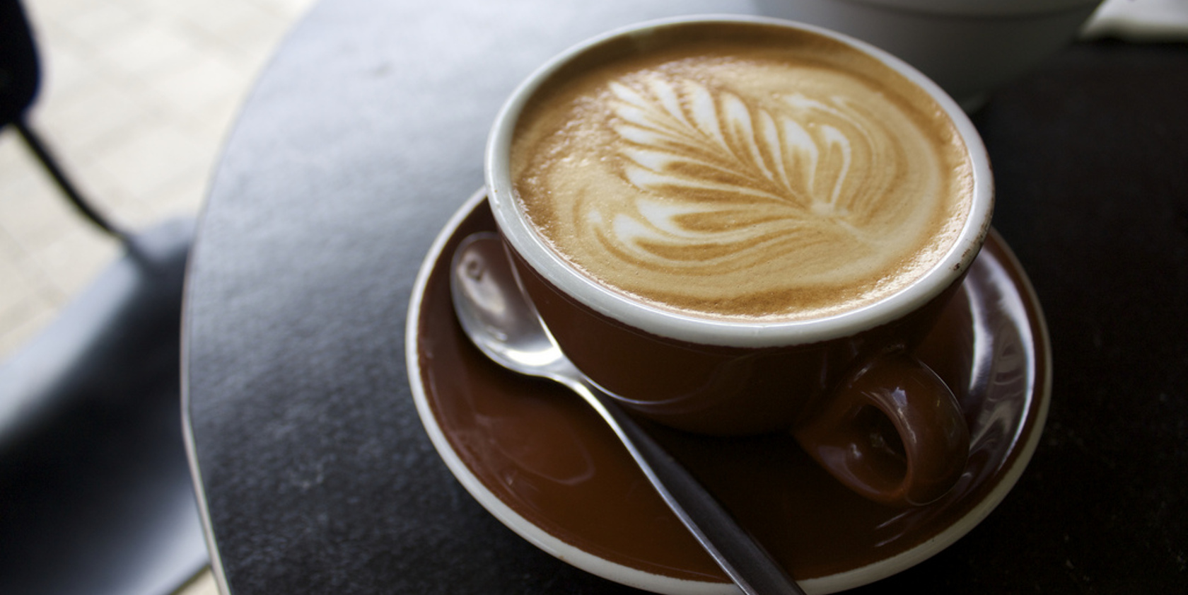 Photographer shot of a cup of coffee with a leaf shape drizzled into the coffee