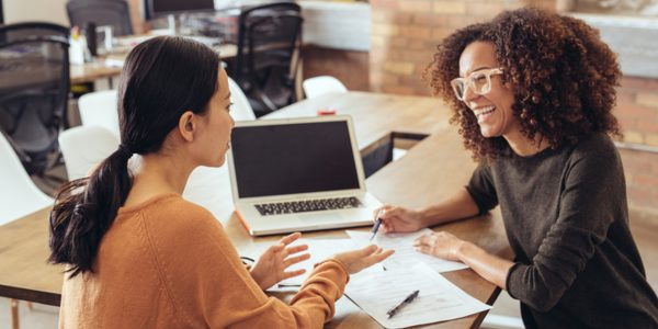 Two women looking at each other laugh over some work
