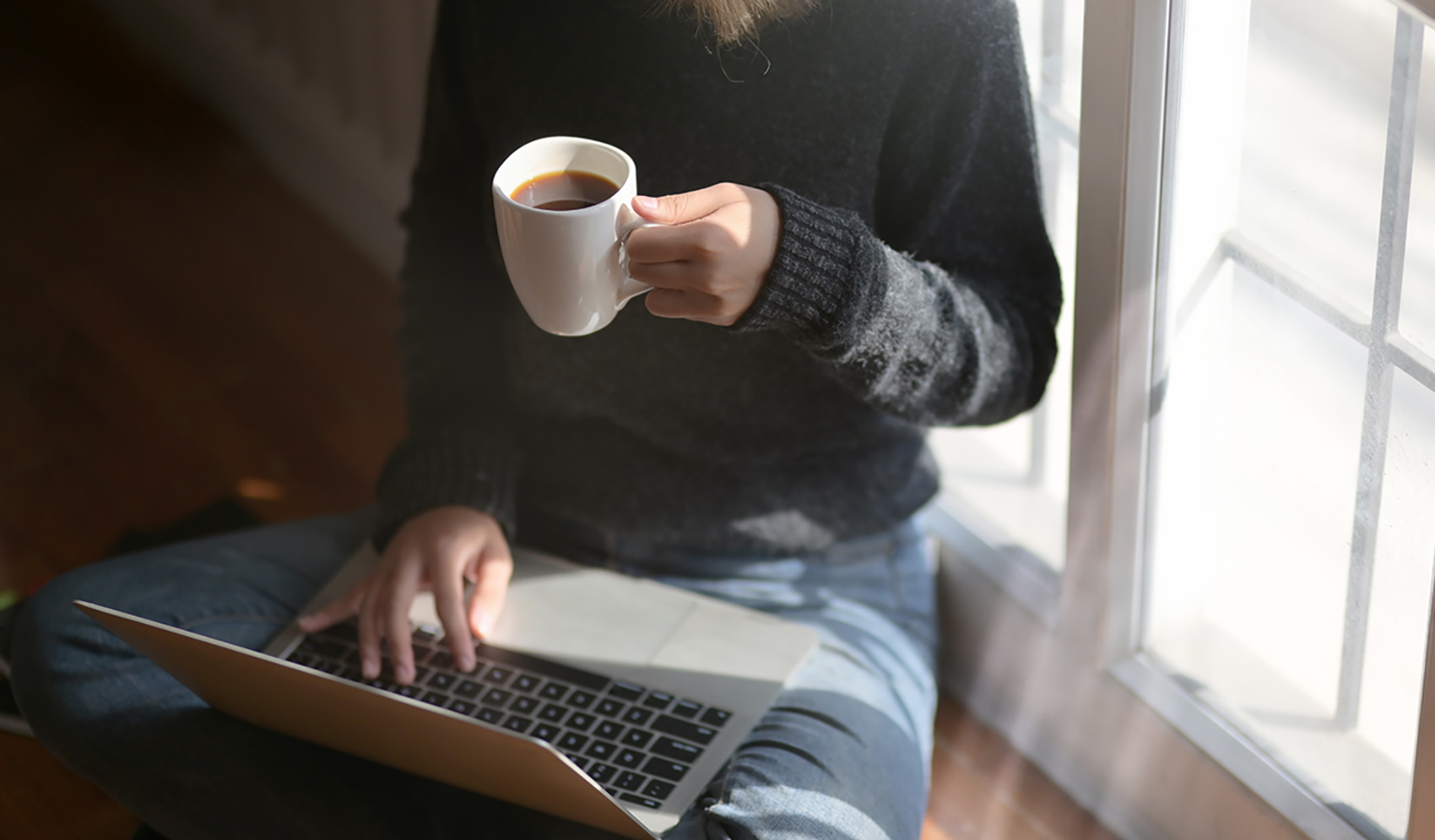 Close-up view of a student working on her project and drinking coffee while sitting near the windows at her workplace