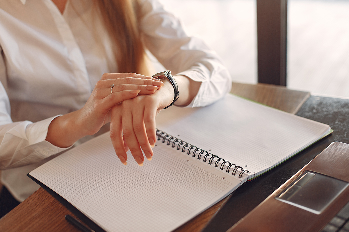 Female entrepreneur checking time while working with papers