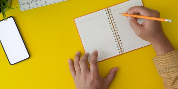 Top view of a man working on his project by writing on notebook
