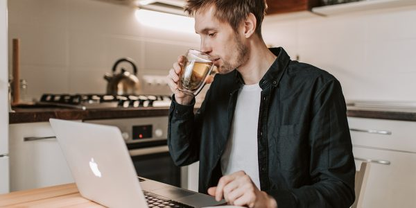 Businessman drinking cup of tea while watching laptop in kitchen at home