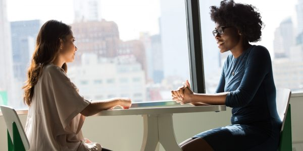 Two women at a table in a discussion