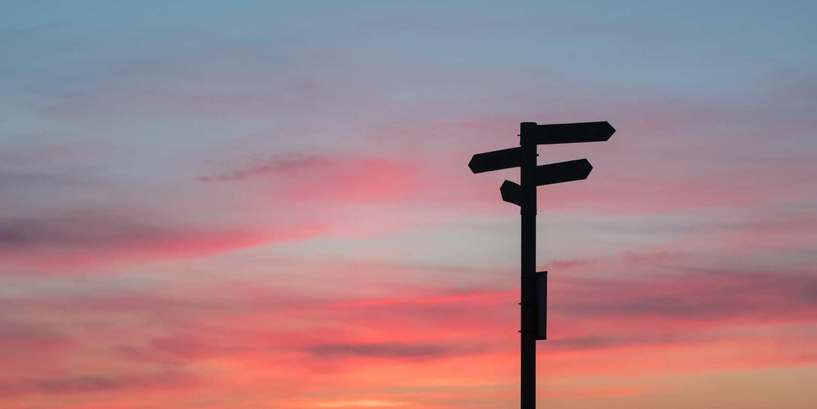 Signpost with diverging directions with a sunset background