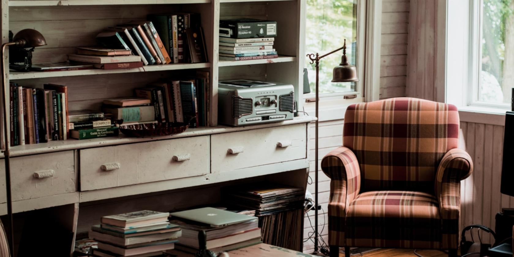 An armchair next to a lamp and bookshelves filled by books and papers