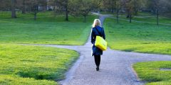 Woman walking towards a crossroads in the path