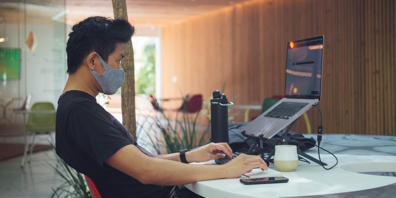 Man wearing mask using a laptop