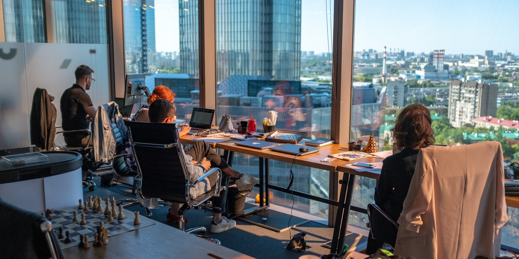 four people working on a long table, high up in a building.