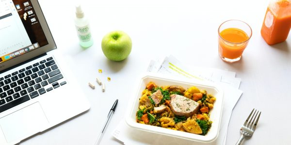 Image of laptop open on a desk with an apple, notebook, pen and lunch.