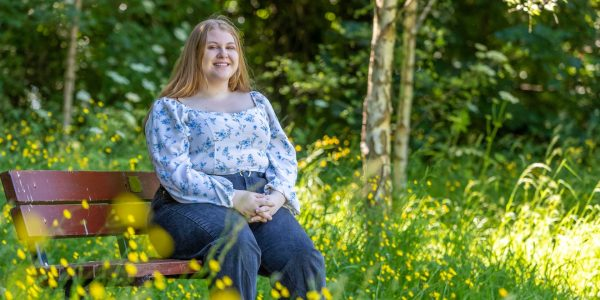 Image of Lowri sat on a bench .