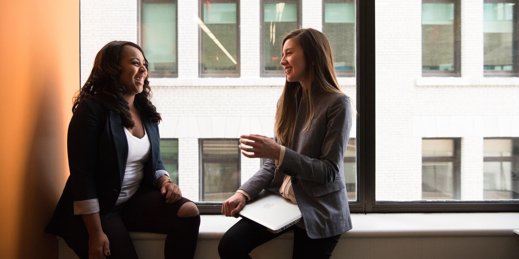 Two women talking on a window ledge in an office building.