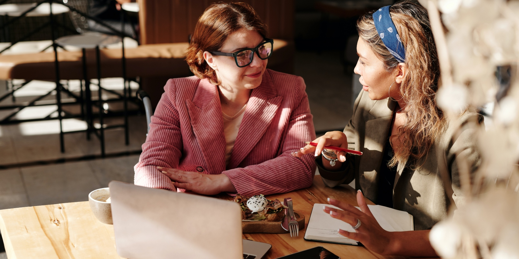 Two females sat together talking with a laptop.