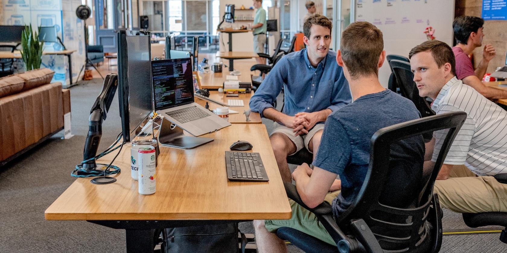 Three men in the workplace talking.