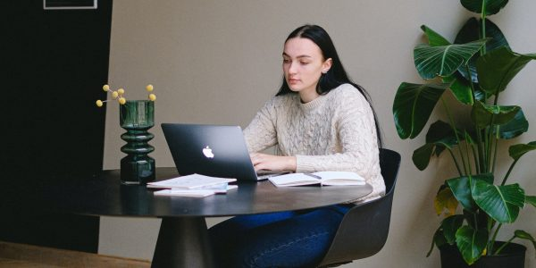 Young woman typing on laptop whilst sat at a desk.