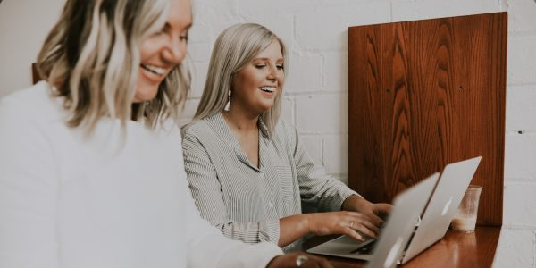 Two women at working on laptops but laughing.