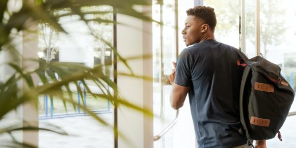 Young man walking out of a door.
