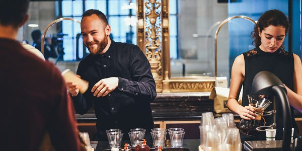 Two people serving drinks in a bar