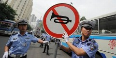 Traffic police in China display a no honking sign to motorists.