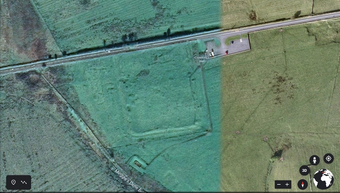 An aerial photograph showing a mainroad cutting diagonally across the top of the image, and intesecting that in a field to the south, is a square enclosure with rounded corners, formed by ditches and banks.