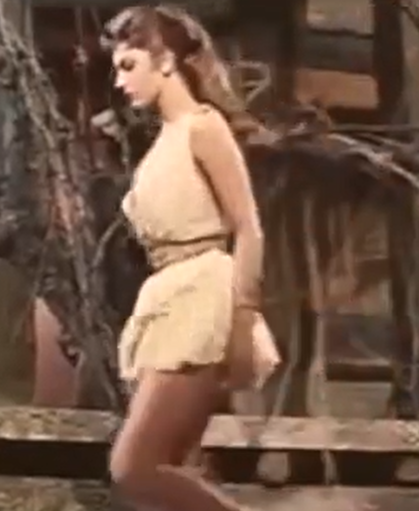 still of a film showing a woman wearing a short white tunic, on board a wooden ship.