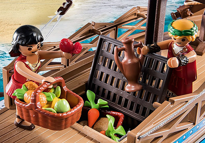 Close up of Playmobil Medea and the contents of her basket, including apples, and two pineapples. Several carrots are also visible in the hold of the vessel, and the trapdoor to the hold is being held open by a chap wearing a laurel wreath and holding an amphora.