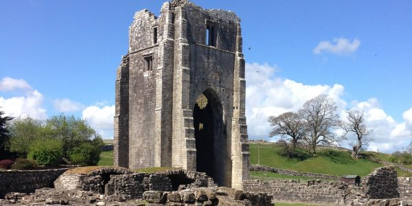 A large central, but ruined tower, with low level walls in the foreground, and a beautiful blue sky beyond.