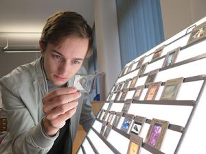 Image of Jamie examines the slide of Picasso's Le Guéridon at lightbox one.