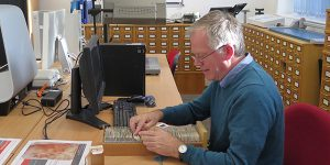 Art Historian Nicholas Alfrey examines a slide drawer in the DHC.