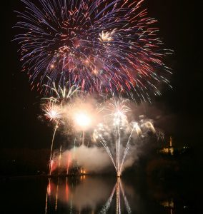 several fireworks explode, reflected in a lake