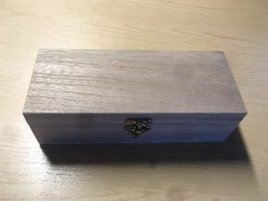 A closed wooden box sits on a desk.