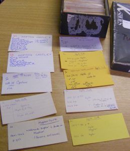 Several index cards with writing and an open shoebox holding more cards