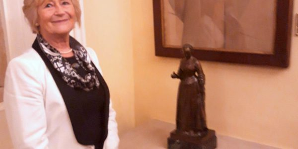 Yvonne Moores standing next to a maquette of Florence Nightingale