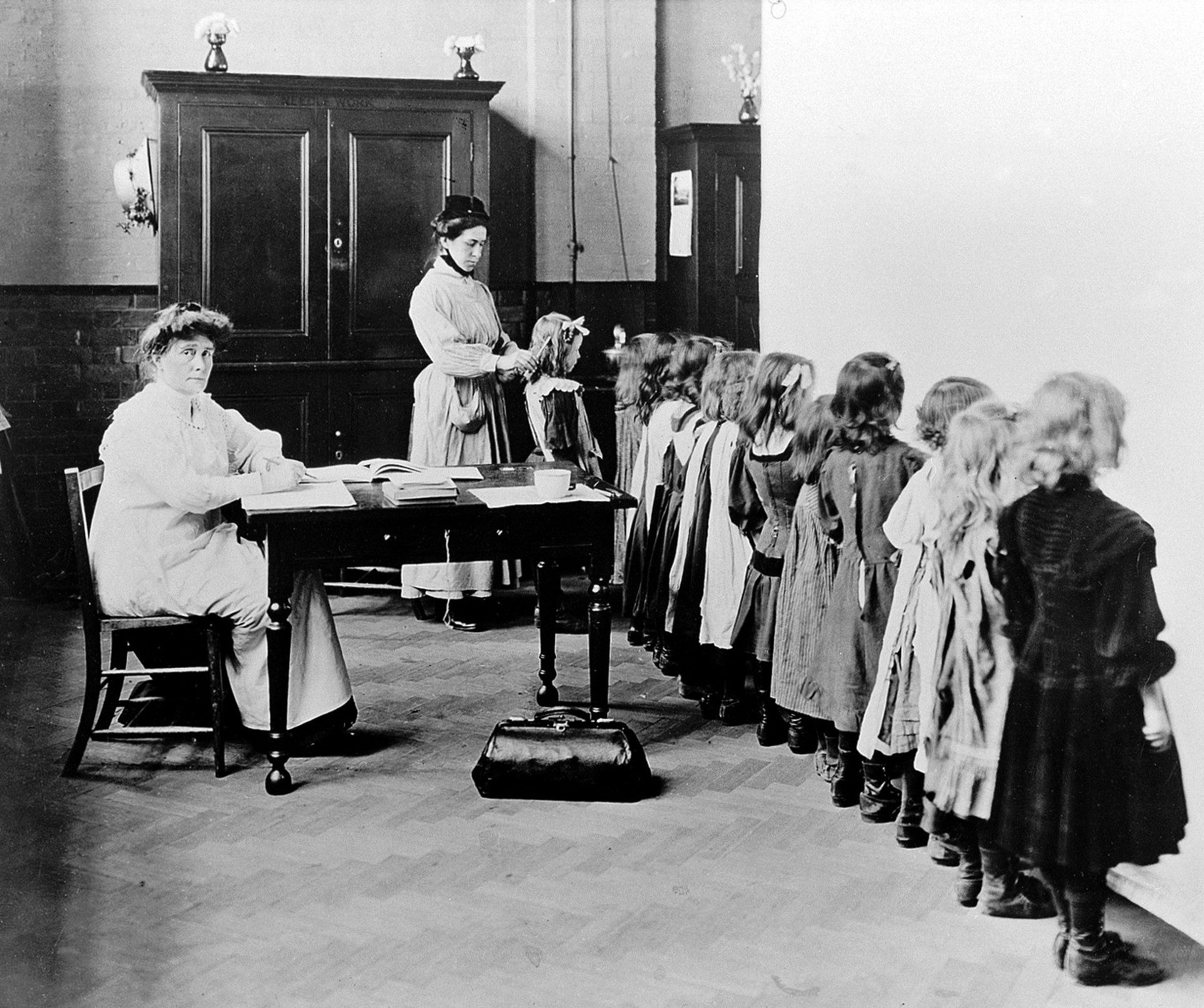 Woman sanitary inspector examining young girls' hair