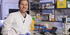 Dr Chris Moore sitting at his work bench with the Oxford Nanopore MinION