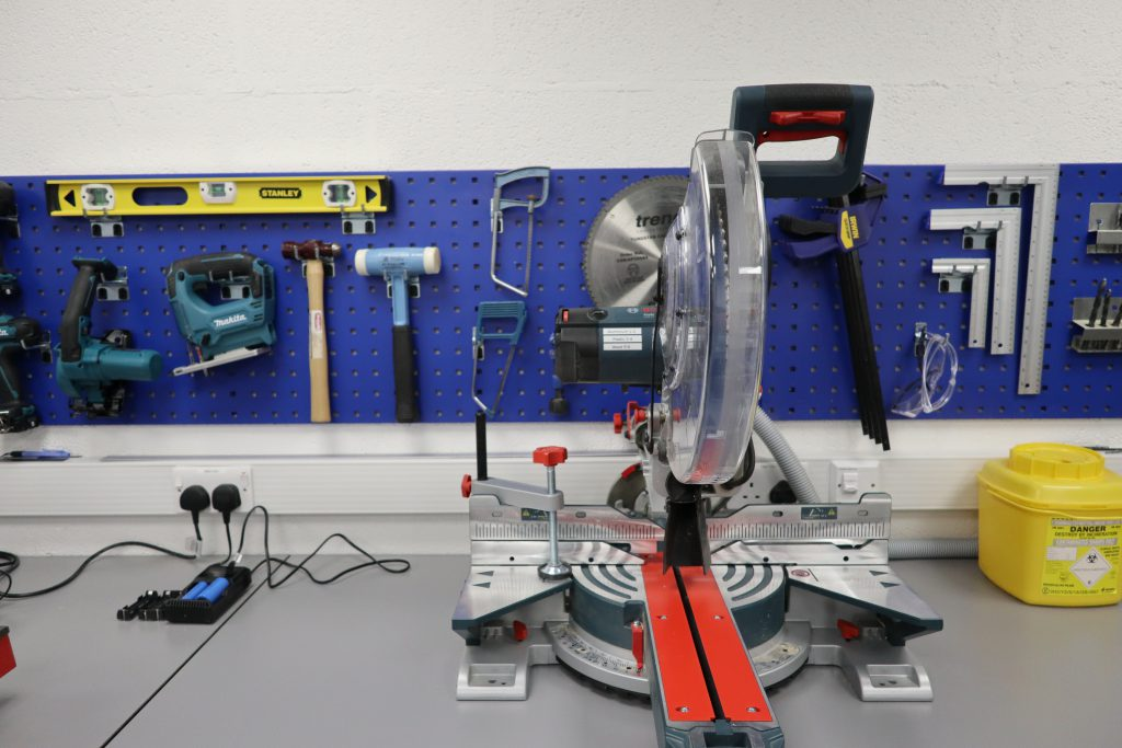 A saw on a workbench with blue board behind holding tools